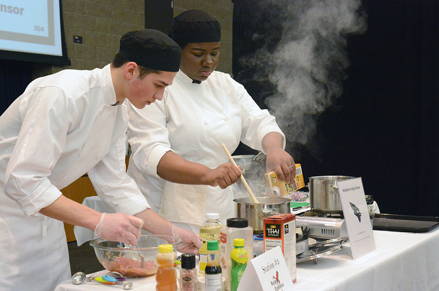 Middleton High School team members Hudson Roberts, at left, and Jade Davis, cook up a honey ginger pork pho dish during the competition.