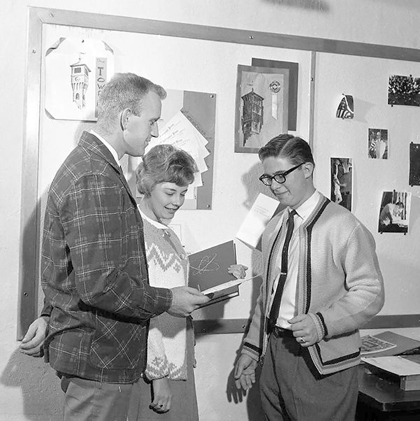 Tower staff members Becky Cranston along with Bill Heuser, left, and Tom Heller look at the All-American Award that the student yearbook received in 1963.