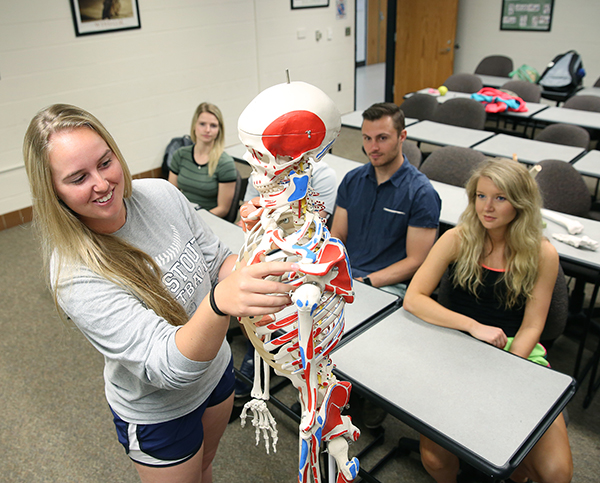 Students work with a skeleton model in a health, wellness and fitness class.
