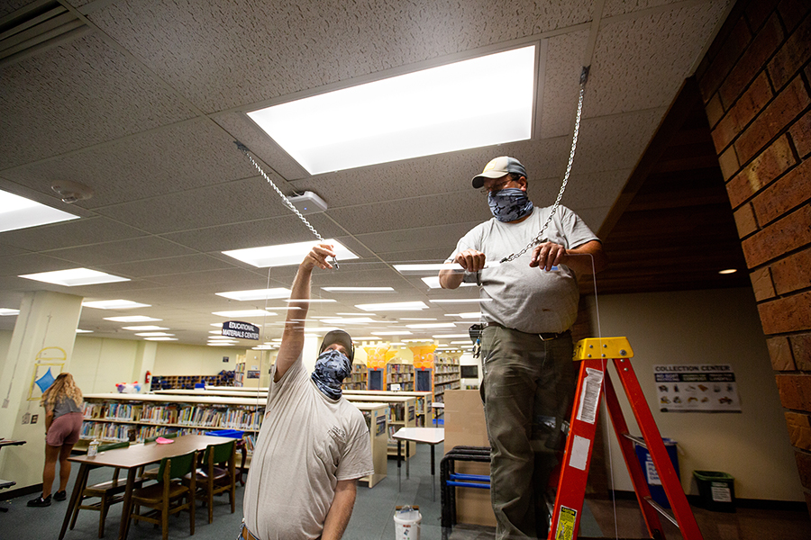 Staff at UW-Stout install a clear barrier in the University Library.