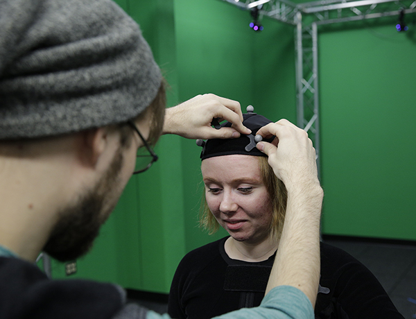 Andrew Fedie adjusts a reflector on the motion capture suit worn by Danielle Pedersen.