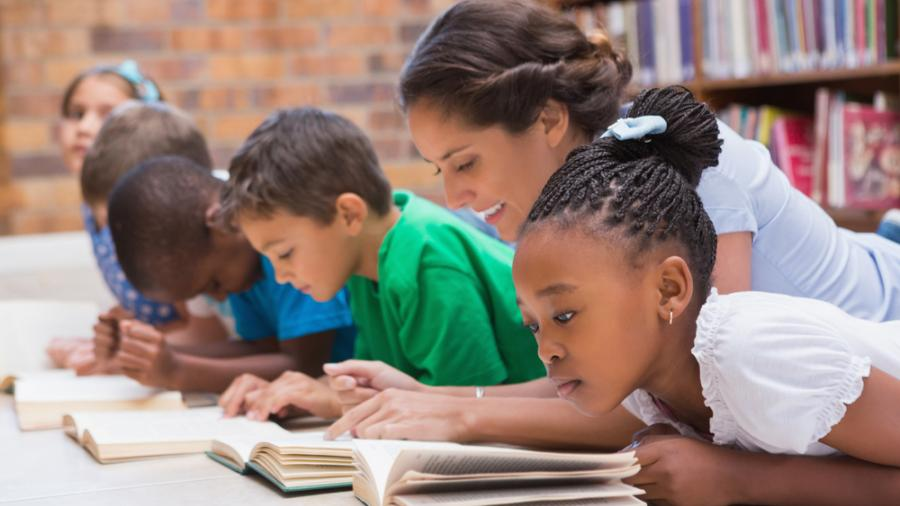 A Teacher Assisting Students Reading.