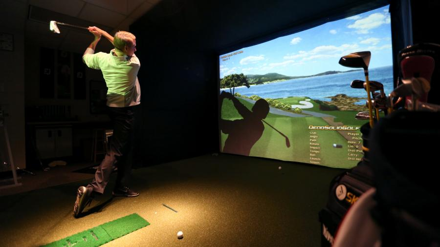 Golf Enterprise Management student on virtual practice turf