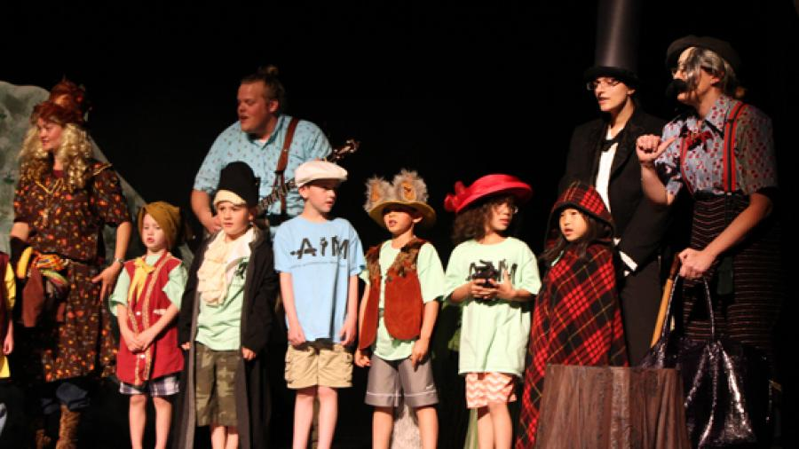 "River Heights kindergarten teachers and students present ""Caps for Sale"" with teacher Det Bossany as Mama Monkey, UW-Stout student Chelsea Kuchinski as Abraham Lincoln and teacher Tanya Staatz as the Peddler. Recent UW-Stout graduate Beau Janke plays the banjo."