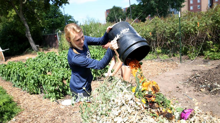 student gardeners are collecting compost from local residents for use in the garden. Pictured dumping fresh compost on the pile is Christina Hammerstrom.