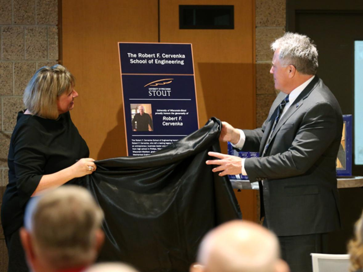 A friend of the Cervenka family, Leslie Lagerstrom, left, unveils a plaque with Chancellor Bob Meyer for the Robert F. Cervenka School of Engineering at a dedication ceremony Friday, Oct. 27, at UW-Stout.
