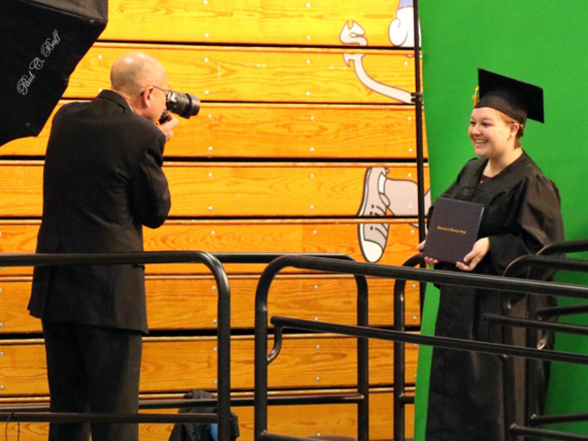 Brittany Jordan has her photo taken after crossing the stage at commencement.