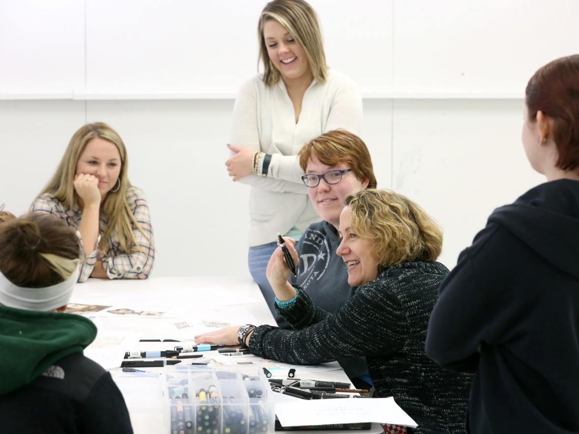 Author and Professor Maureen Mitton, second from right, works with interior design students in a class