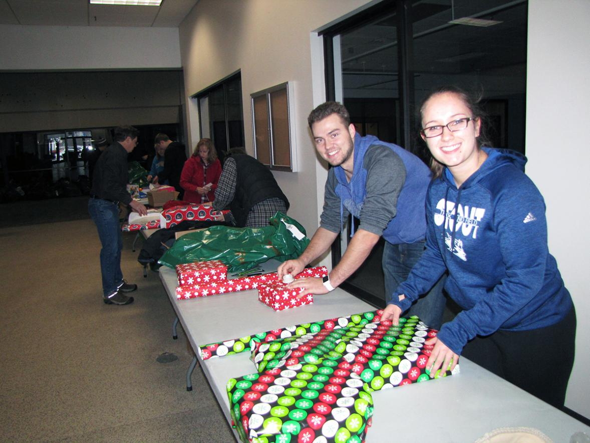 UW-Stout students Walker Olson, at left, and Andrea Bertram volunteered to wrap gifts on Dec. 1 for the Road to Freedom's Motorcycle Rights Organization's Christmas Miracle that helps area children in need get needed items and toys for Christmas./UW-Stout photos by Pam Powers
