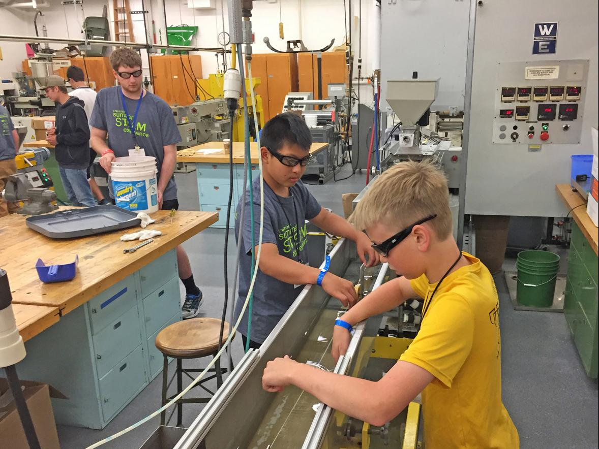 UW-Stout Summer STEAM Experience camp members Ryan Xu, at left, and Tanner Husby, guide filament being extruded for 3D printers in the plastics laboratory on campus.