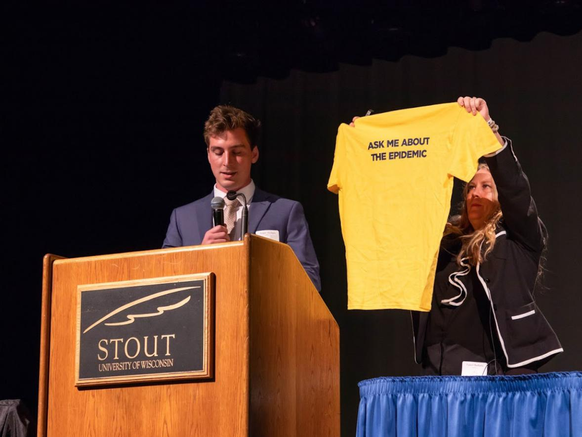 Lauri Badura holds up a t-shirt for an organization she started in memory of her son to help those with drug addiction during the Health Dunn Right conference Tuesday at UW-Stout. Her son, August, at left, also spoke.