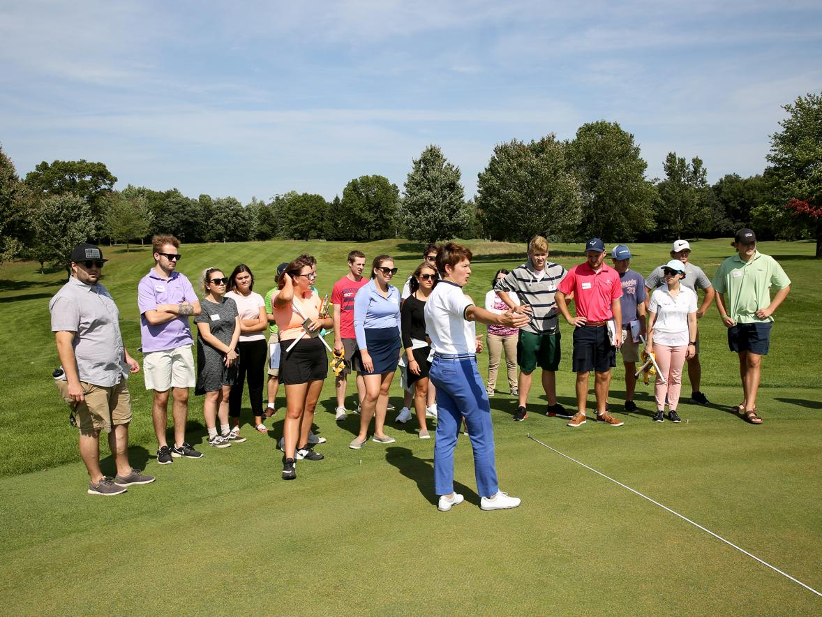 A Sports Event Management class listens to Associate Professor Kris Schoonover at Tanglewood Greens, where the Tees Fore Tuition event will be held.