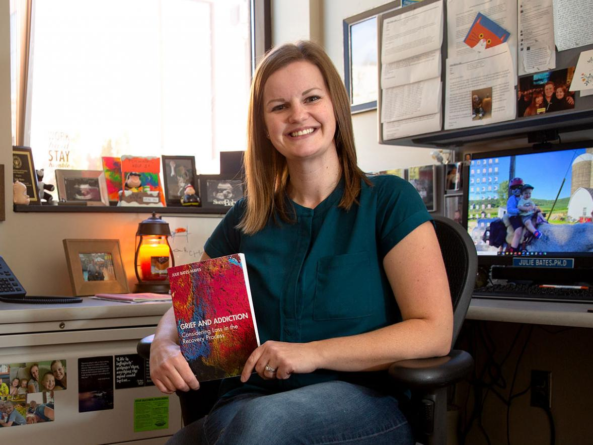 "Associate professor Julie Bates-Maves with her newly published book ""Grief and Addiction""."