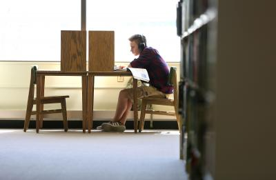 Student studying a desk in the library.