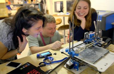 Three students working with a 3D printer in a Fab Lab.