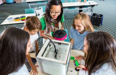 Students and teacher at a 3D printer in a Fab Lab.